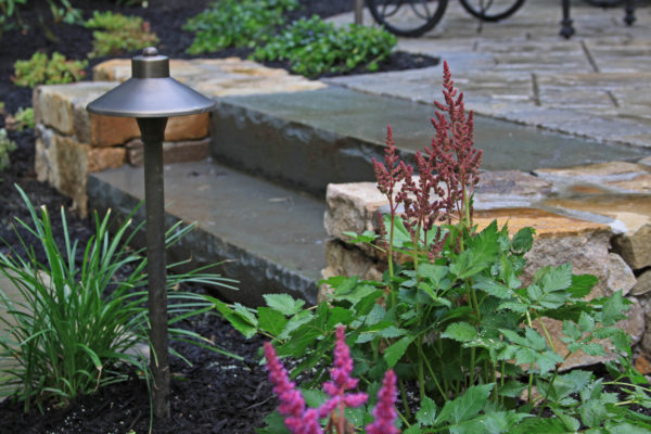 Astilbe in front of bluestone slab step and stone wall in new jersey Madlinger Exterior Design