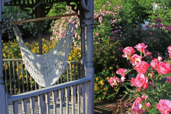 Madlinger Exterior Design Gazebo swing surrounded by flowers in new jersey Madlinger Exterior Design-min