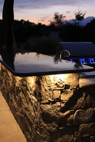 Madlinger Exterior Design stone outdoor kitchen with led lighting shining down on the stone with granite coutner tops and lynx bbq in flemington new jersey-min