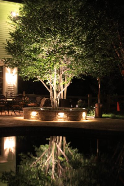Madlinger Exterior Design stone seat wall with down lighting and up lighting on tree around swimming pool in basking ridge new jersey-min