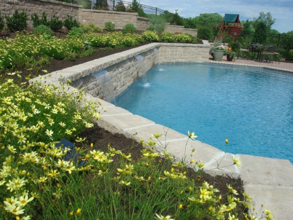 Madlinger Exterior Design swimming pool with waterfalls backed by tiered retaining wall in Annadale New Jersey-min