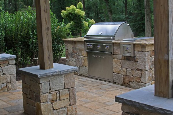 Outdoor kitchen with granite counter top behind deck pillars wrapped with stone in Basking Ridge New Jersey Madlinger Exterior Design-min