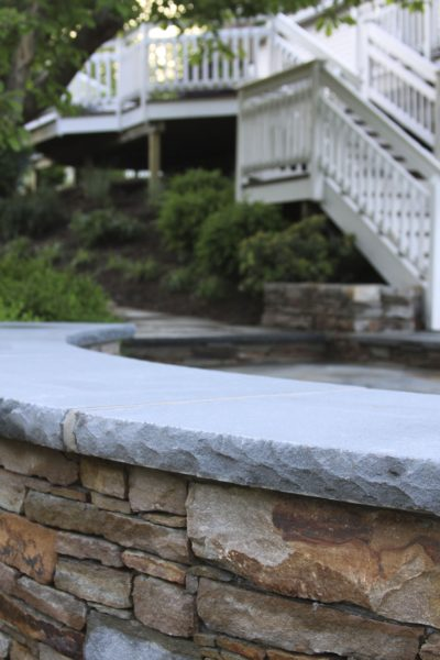 Stone seat wall with curved bluestone cap backed by bluestone patio and plantings in new jersey Madlinger Exterior Design-min