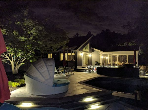 Porcelain tile pool patio at night with landscape lighting shining on stone steps and plantings in Morristown, NJ