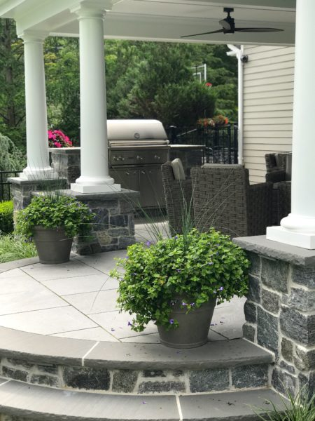 Raised porcelain tile patio with bluestone curved steps and outdoor kitchen in Mendham, NJ