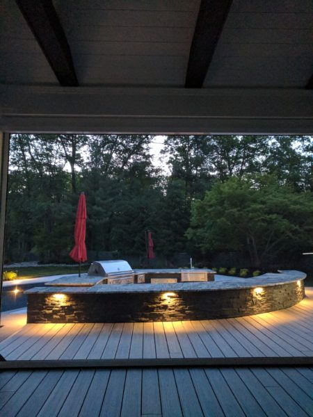 Covered roof structure with automatic screen backed by outdoor kitchen with built in landscape lighting in Morristown, NJ