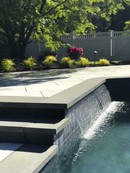 Porcelain pool patio with waterfall in Morristown, NJ