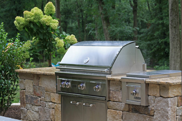 Stone outdoor kitchen with granite counter top and Lynx grill in Basking Ridge, New Jersey